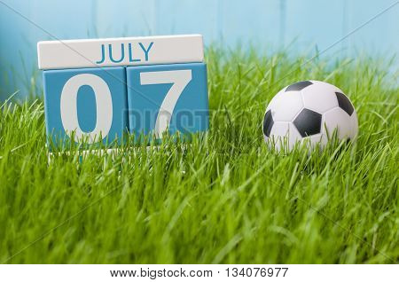 July 7th. Image of july 7 wooden color calendar on greengrass lawn background. Summer day, empty space for text.
