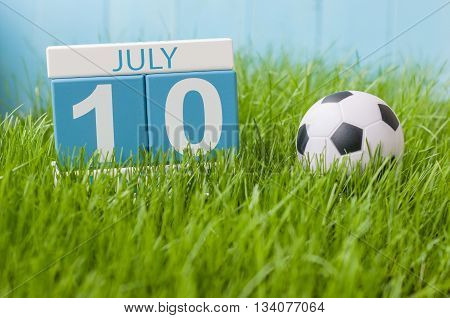 July 10th. Image of july 10 wooden color calendar on greengrass lawn background. Summer day, empty space for text.