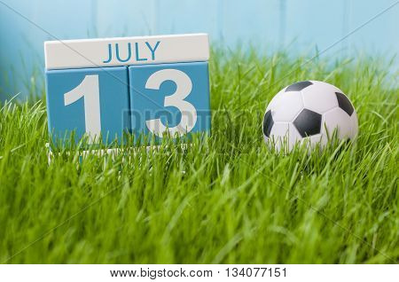 July 13th. Image of july 13 wooden color calendar on greengrass lawn background. Summer day, empty space for text.