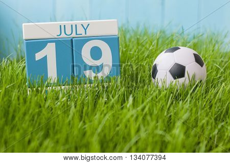 July 19th. Image of july 19 wooden color calendar on greengrass lawn background. Summer day, empty space for text.