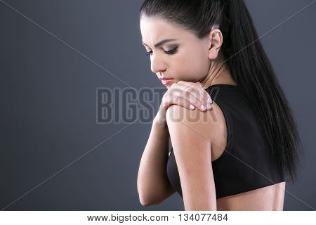 Body pain. Studio shot of beautiful young woman with dark brown hair. Woman suffering from shoulder pain