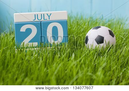 July 20th. Image of july 20 wooden color calendar on greengrass lawn background. Summer day, empty space for text.