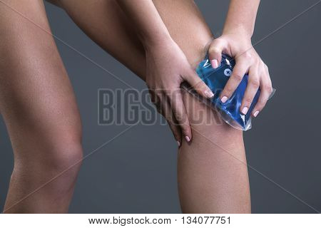 Body pain. Close up studio shot of woman. Woman suffering from knee pain. Woman holding freezing gel on knee