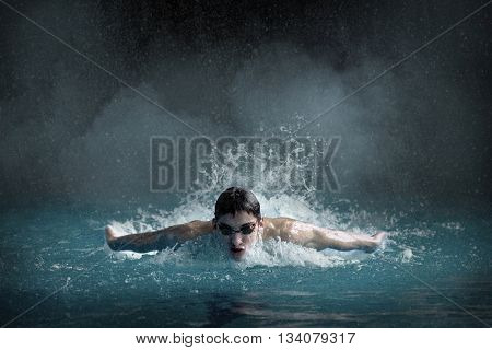 Swimer in waterpool. Butterfly style of swimming.