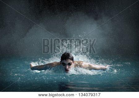 Swimer in waterpool. Butterfly style of swimming.