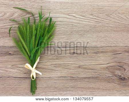 Cute bouquet of spikelets on wooden table with copy space. Flat lay top view