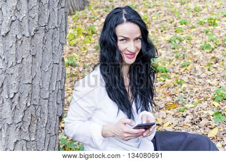 Caucasian brunette writing sms by cellular in autumn park