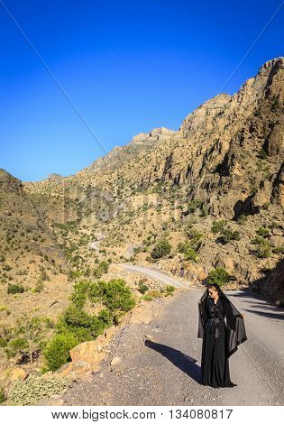 A woman in black abaya is walking on a road in Al Hajar Mountains in Oman