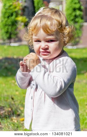 Portrait of eating baby girl with curly blond hair