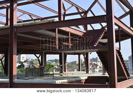 Metal frame building under white brick building