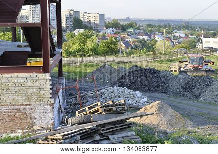 Construction materials and waste on the background of building under construction.