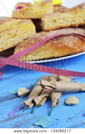 some firecrackers and a plate with pieces of coca de Sant Joan, a typical sweet flat cake from Catalonia, Spain, eaten on Saint Johns Eve, on a rustic blue table with confetti and streamers