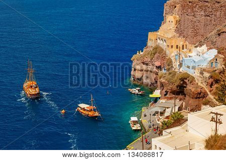 Fishing and motor boats in Mesa Gialos, Old Port of Fira, modern capital of the Greek Aegean island, Santorini, in the sunny day, Greece