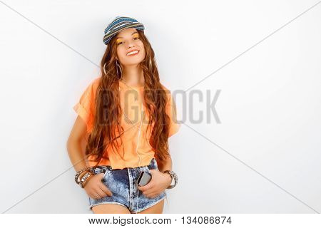 beautiful woman wearing blue cap in orange T-shirt standing near white wall and smiling, fashion concept
