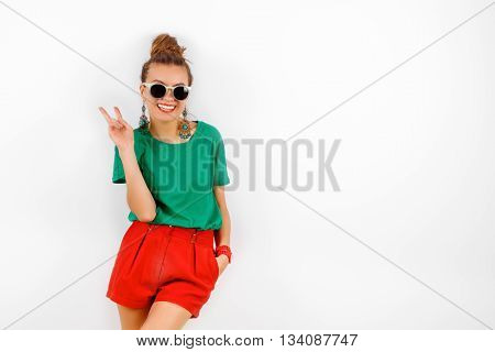 beautiful woman in sunglasses wearing in red shorts and green T-shirt standing near white wall, smiling and shows victory, fashion concept