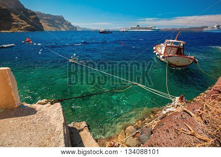 Fishing Boat, motor boats and cruise liners in Mesa Gialos, Old Port of Fira, Santorini, in the sunny day, Greece.