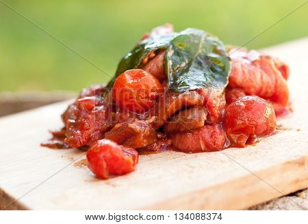 Beef meat marinating in balsamic vinegar olive oil tomatoes and basil