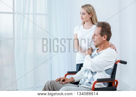 Adult man in wheelchair. White interior with big window. Sad man looking at window. Young helper is near him