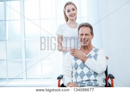 Adult man in wheelchair. White interior with big window. Man and young helper smiling and looking at camera
