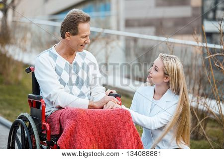 Adult man in wheelchair during walk. Man and young helper smiling. Nurse carrying patient on wheelchair