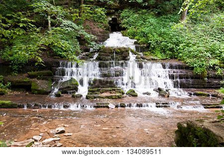 Waterf flows directly from rock on a limestone cliff.