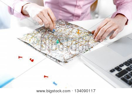 Concept for travel agent. Close up photo of young woman. Woman choosing travel destination on map. Travel agency office interior