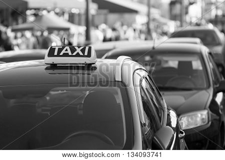 symbol or sign with an inscription of a taxi is located on a car roof on an indistinct background city street of monochrome color
