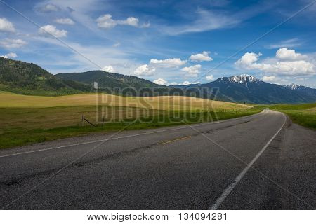 Road with one point perspective driving car to rugged rocky Teton snow capped mountain range blue sky majestic landscape scene with dramatic clouds