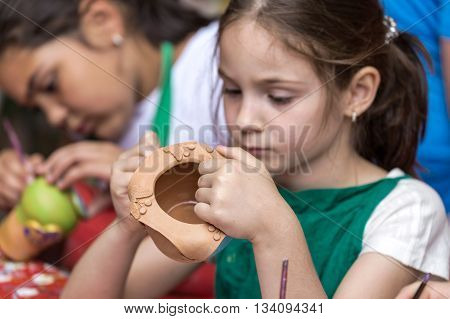TIMISOARA ROMANIA - JUNE 1 2016: Girls who paints a ceramic bowl. Workshop organized by the City Hall Timisoara with the occasion of the International children Day.