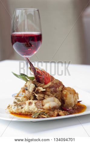 Frieds shrimp cooked in thai style with a glass of red wine