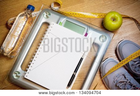 Sneakers centimeter green apple notebook scale bottle of water. Weight loss healthy lifestyle concept