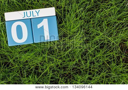 July 1st. Image of july 1 wooden color calendar on green lawn grass background. Summer day.