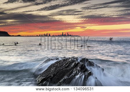 Currumbin Rock Gold Coast sunset with surfer silhouettes and ocean current rushing against a large rock