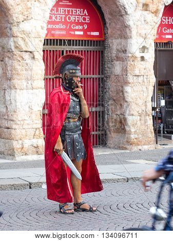 Verona Italy September 27 2015: Man dressed as a Roman legionary smokes near the Arena on Piazza Bra in Verona Italy