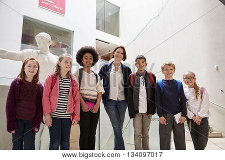 Portrait Of Teacher With Class Standing Inside Museum