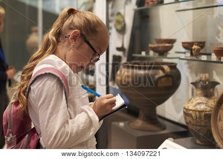 Student Looking At Artifacts In Case On Trip To Museum