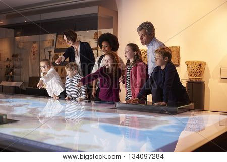 Pupils On School Field Trip To Museum Looking At Map