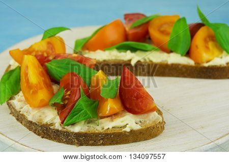 Bruschetta with soft cheese basil and cherry tomatoes on a wooden background. Easy Vegetarian Italian healthy snack.