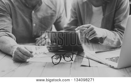 Coworkers team brainstorming process modern loft.Project producer reading report tablet, glasses wood table.Young business crew working startup studio.Using Laptop.Blurred, film effect. Black White