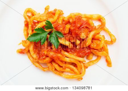 Traditional Tuscan pici pasta with tomato sauce shot from above