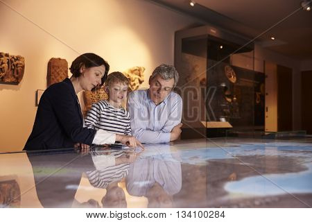 Family On Trip To Museum Looking At Map Together