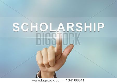 business hand pushing scholarship button on blurred background