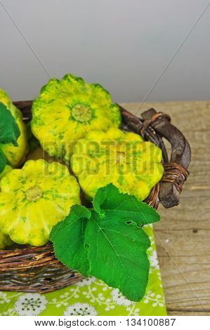 Scalloped Squash Pattypan on bamboo basket on a wooden background. Eco vegetables.