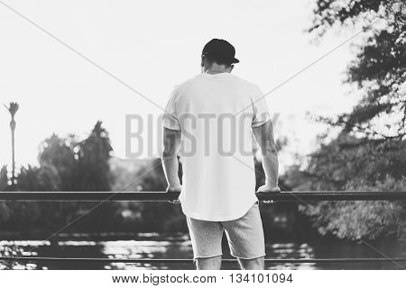 Bearded Muscular Man Wearing Blank t-shirt, snapback cap and shorts in summer time.Relaxing time near the lake.Green City Garden Park Sunset Background. Back view. Horizontal Mockup.Black White.