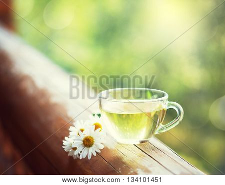 Cup of herbal tea on the railing of the balcony. Toned image