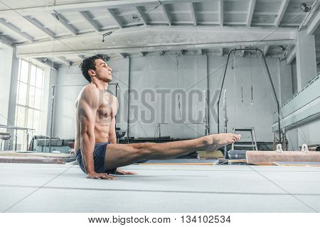 The caucasian man gymnastic acrobatics equilibrium posture at gym background