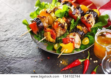 Light summer lunch grilled chicken and vegetable skewers served with served with vegetables