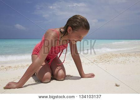 Kneeling girl looking at a tiny crab on a white sand beach
