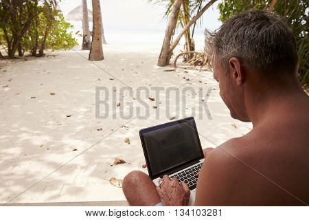 Man using a laptop computer on a beach, over shoulder view
