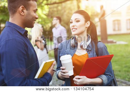 Pretty two friends are chatting near a university. They are standing and smiling. Man and woman are holding studying material